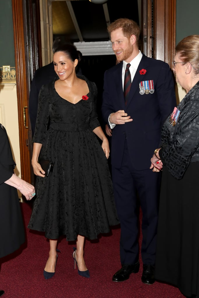 On Saturday, the royal family reunited publicly for the first time in months to attend the Royal British Legion's Festival of Remembrance at the Royal Albert Hall. Prince William, Kate Middleton, Prince Harry, and Meghan Markle joined Queen Elizabeth II for a sombre evening of reflection before Remembrance Sunday, where they honour military members who died in war.  This is Meghan's second round of remembrance events since becoming a royal last year. She chose a sophisticated black brocade dress by Erdem for the occasion. Fun fact: Erdem appears to be a favourite designer for Meghan, as well as for her sister-in-law, Kate. Meghan's retro pick featured an A-line skirt which hit right above her knee, a belted waist, and buttons down the front. The Duchess of Sussex completed the look with a trusty pair of Jessica McCormack hoop earrings, her Aquazzura pumps, and the traditional red poppy pin. Ahead, see more photos of her full outfit.