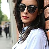 A chunky chain offset this preppy-style button-down, as did her round shades. Source: IMAXtree