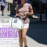 Rachel sported a laid-back daytime look with white denim shorts, a mauve tee, and ankle-strap sandals — the perfect example of how her boxy Chanel bag can dress up even the most casual of looks.