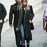 In December 2016, Jennifer wore a long black coat over a button down shirt, straight jeans, and ankle boots.