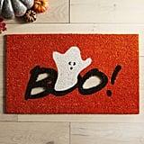 حصيرة برتقاليّة تحمل كلمة Boo مفرّغة من علامة Pier 1 Imports (بسعر 12$ دولار أمريكي؛ 30 درهم أماراتيّ/ريال سعودي. سعرها الأصلي 20$ دولار أمريكيّ؛ 50 درهم إماراتيّ/ريال سعودي).