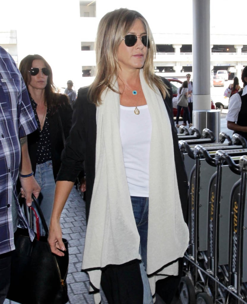 """Jennifer Aniston was spotted grabbing a flight out of LA on Tuesday. The actress kept things casual in jeans and a white tee, which she layered with a long sweater and scarf. It's the first glimpse we've gotten of Jen since she published her headline-making Huffington Post essay earlier this month; in the personal piece, Jennifer railed against """"the objectification and scrutiny we put women through"""" and revealed that she's """"fed up"""" with being the subject of pregnancy rumors and body shaming. One big fan of the essay was Jennifer's husband, Justin Theroux, who gave her a shout-out on Instagram the following day by calling her his """"#WCW."""""""