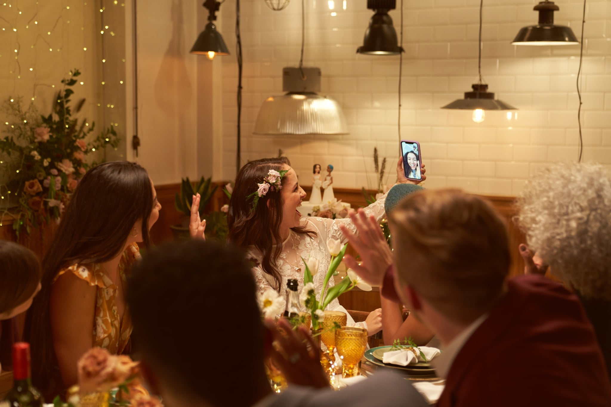 Two married girls having a wedding dinner party with some of their close  friends and another friend makes a video call