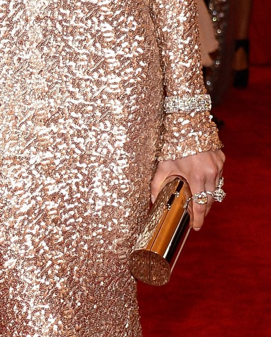A sleek gold clutch offsets the allover sequin sparkle.