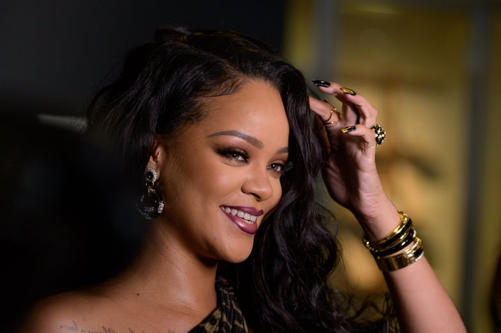 Rihanna attended the NYC Porcelain Ball this weekend with a beauty look so hot, parts of it seemed like they were melting. The singer's nails were painted black and featured gold polish dripping down a few accent nails. Her go-to manicurist Maria Salandra posted an image of matte black candles with gold wax dripping down the side, which can be assumed to be the inspiration for this creative drip manicure. While we've seen this nail art before, we can't get over how luxe it looks in this black-and-gold color palette. Ahead, check out Rihanna's nails and the rest of her steamy beauty look.