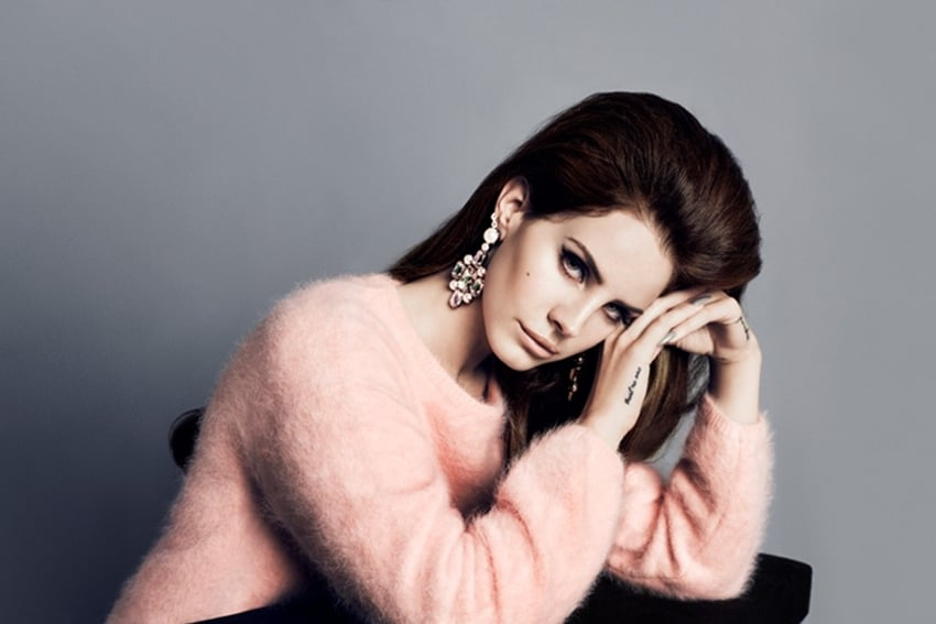 High-volume hair paired with bedazzled earrings and a pink sweater complete her retro look.
