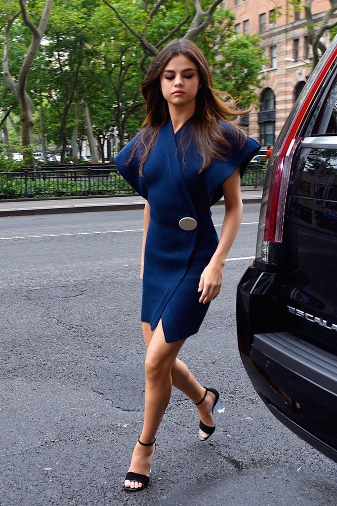 We've already dubbed Selena Gomez the reigning queen of Spring street style, and her latest outfit just further proves she's beyond deserving of her hypothetical throne and crown. The star was recently spotted out and about in New York City looking as polished and elegant as ever. At first glance, we thought her dress — a navy blue number with a large button closure and exaggerated shoulders — was a modest choice. But then she turned to the side and we immediately noticed how the dress showed just the right amount of skin beneath its billowing shoulders.  She paired her Jacquemus wrap dress with a pair of simple ankle-strap heels by Louis Vuitton. Ahead, shop Selena's exact dress, along with other similarly chic options.      Related:                                                                                                           Selena Gomez Found the Summer Top to Wear With Blue Jeans