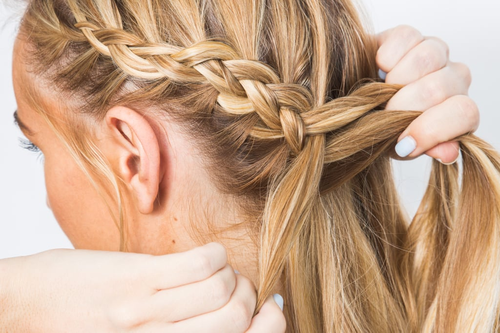 Create a side part. Make a dutch braid from temple to nape, bringing the braid around behind the opposite ear. Make sure to leave a little bit of hair out around the ear to frame the face. Leave out any bangs, too.