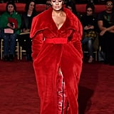 Opening Christian Siriano's show wearing a fuzzy red coat, thigh-high boots, and a red belt.
