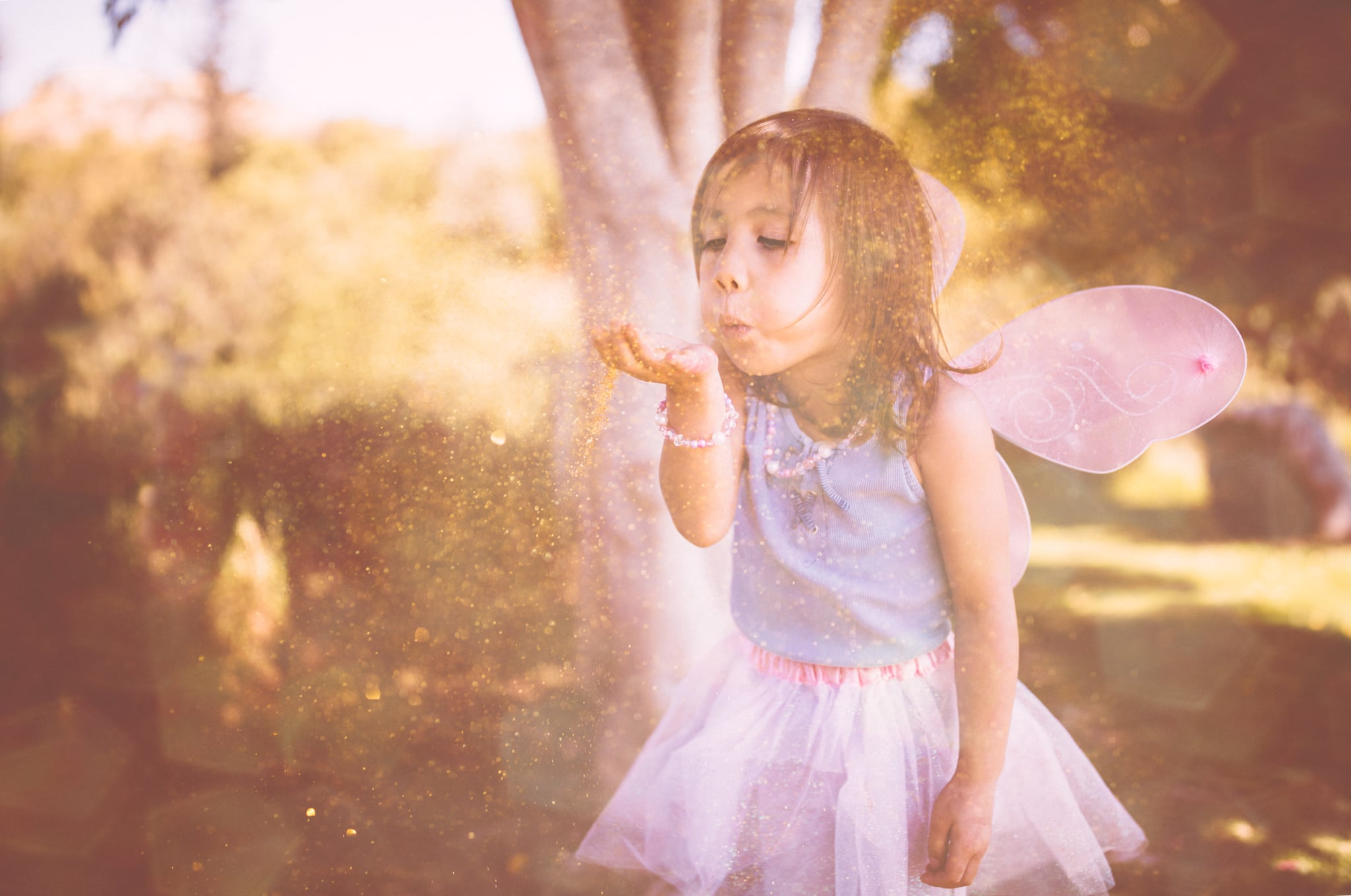 Asian girl dressed as fairy blowing glitter and having fun in the garden in spring