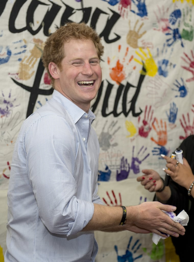 Prince Harry showed off his sense of humour when he planted a purple handprint on a royal photographer's head in New Zealand on Friday. He was visiting the Turn Your Life Around Trust for at-risk youths in Auckland when his hand was painted bright purple so that he could put his handprint on a mural. With a smirk on his face, though, he quickly turned around and put his hand on the head of photographer Arthur Edwards, making everyone in the room crack up. Watch the funny moment in the clip below, then check out the most hilarious signs fans have made for Prince Harry and see the sweet reunion he had in New Zealand with a former teacher.  Prince Harry plonks a purple handprint on @arthurjedwards's head at #TYLA #RoyalVisitNZhttps://t.co/5r39EPal7p— The Duke and Duchess of Cambridge (@KensingtonRoyal) May 15, 2015