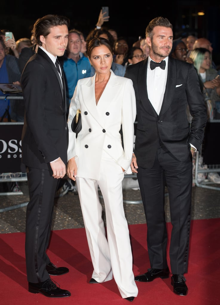 Victoria and David Beckham made quite a stylish pair at the 2019 GQ Men of the Year Awards on Sept. 3rd. The couple walked the red carpet with son, Brooklyn, wearing complementary suits — his, his, and hers, if you will. David received GQ's editor special award that evening, celebrating 20 years since his very first cover with the magazine.  For the momentous occasion, Victoria chose a sophisticated white double breasted suit with contrasting buttons. She tied the look together with black stilettos, a matching clutch, and subtle jewel earrings. Her outfit stood out between David and Brooklyn, who opted for classic tuxedos. Keep reading for more photos of their night on the red carpet, from all angles. This family means business — as if there was any doubt before.