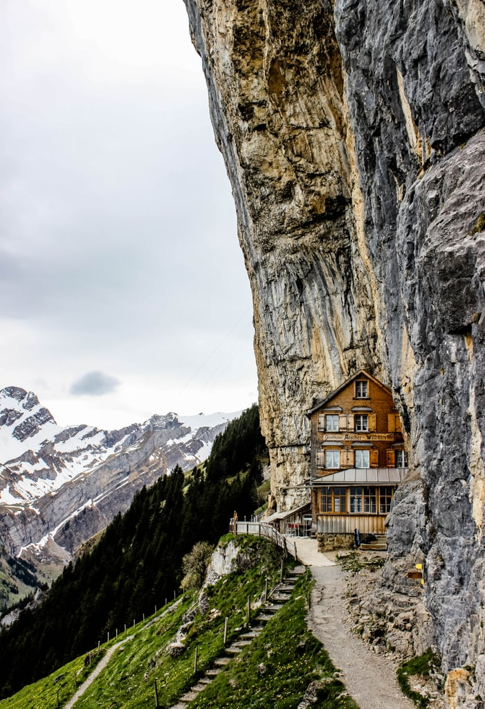 """Have you ever heard of Berggasthaus Aescher-Wildkirchli? Built over 170 years ago to originally house farmers and their livestock, this mountain hut perched high above in the Swiss Alps has since evolved into one of the most unique restaurants in the world.  What makes this place so fascinating is how it was precariously built into the side of the mountain and still, to this day, clings to the foot of a vertical cliff. Now, is it just me, or does this place take adventurous eating to a whole new level!? Yet, you'll really have to work for this one-of-a-kind Swiss meal, as getting to this cliffside restaurant won't be any ole simple task. To even access this mountain eatery, you'll have to ride an aerial cable car and hike through a prehistoric cave. But don't worry — once you arrive, you'll be welcomed with a picturesque panorama of the Alpstein mountain chain, giving the phrase """"dinner with a view"""" an entirely new meaning. Sound like your kind of thrilling adventure? Take a look at these awe-inspiring photos for a step-by-step guide as to what to expect at this exhilarating Swiss destination."""