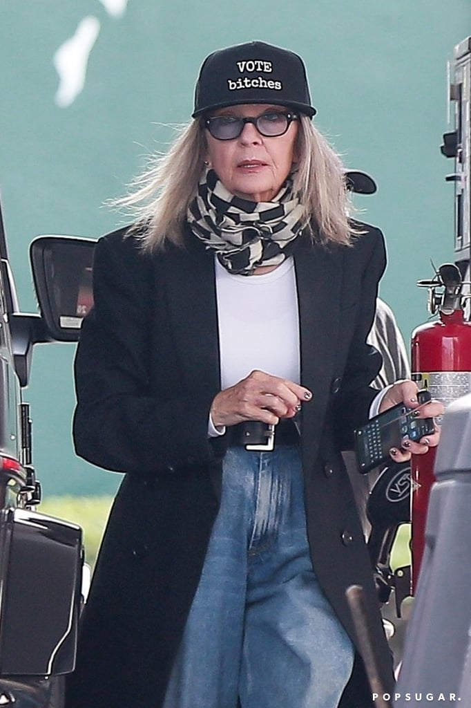 """Diane Keaton has an extensive and well-documented hat collection. In fact, she modelled her many chapeaus in a wildly entertaining, three-minute video shared to Instagram in July. """"At this time of such sadness and worry, a friendly hat and a friendly face makes the day,"""" Diane said. Her latest acquisition, however, is a more timely and urgent one: While recently running errands, the iconic actress sported a black baseball cap that bluntly states, """"Vote bitches.""""  Though markedly different than Michelle Obama's trendy election merch, Diane's hat gets the point across just fine. We'd also be remiss not to mention the rest of her outfit, which consisted of a patterned infinity scarf, classic white T-shirt, black double-breasted coat, heeled loafers, and belted blue jeans with a wide leg. In essence, it is the perfect fall outfit. While we have you here . . . please read up on some of the ways you can safely vote in person or ensure that your mail-in ballot is counted ahead of election day on Nov. 3. If you're eligible to vote but aren't already registered, you can do so by filling out this easy form that takes about two minutes to complete. Let's all just make sure to do as Diane says, alright?       Related:                                                                                                           Show Off the Fact That You're a Voter With These 15 Cute Pieces"""