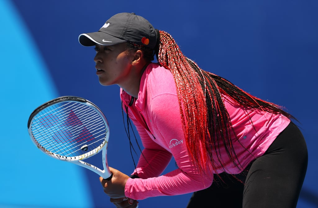 """Naomi Osaka is celebrating her spot on Team Japan. The 23-year-old tennis champion is gearing up to make her Olympics debut at the upcoming Summer Games in Tokyo. In 2019, Osaka announced she would be relinquishing her US citizenship to represent her birth nation in the storied international sporting event, and just days before it begins, Osaka arrived to practice at the Ariake Tennis Park wearing braids seemingly commemorating that decision.  Though she has yet to explicitly share the inspiration behind her new hairstyle, Osaka's braids closely resemble the colours of the country's flag: red with white strands sparingly woven throughout. In photos from practice, Osaka is shown closely inspecting her patriotic, waist-length braids. Her french manicure also fit the theme, with one hand bearing red tips and the other white.  Osaka has previously said she's afraid to wear her hair in anything other than a bun while competing because she's won so many matches while wearing the hairstyle. She tweeted in 2018, """"No lie, now I'm scared to wear a ponytail."""" A few years and several Grand Slams later, however, we think she'll be fine regardless.  Take a closer look at Osaka's red braids at practice ahead.      Related:                                                                                                           For Olympic Runner Christina Clemons, Bold Hair and Makeup Looks Are Her """"Super Power"""""""