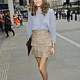 Olivia gave a Reiss basic knit a fashion-forward twist with a tiered Matthew Williamson miniskirt and a pair of metallic cap-toe pumps by Elizabeth and James at the Matthew Williamson show in London.