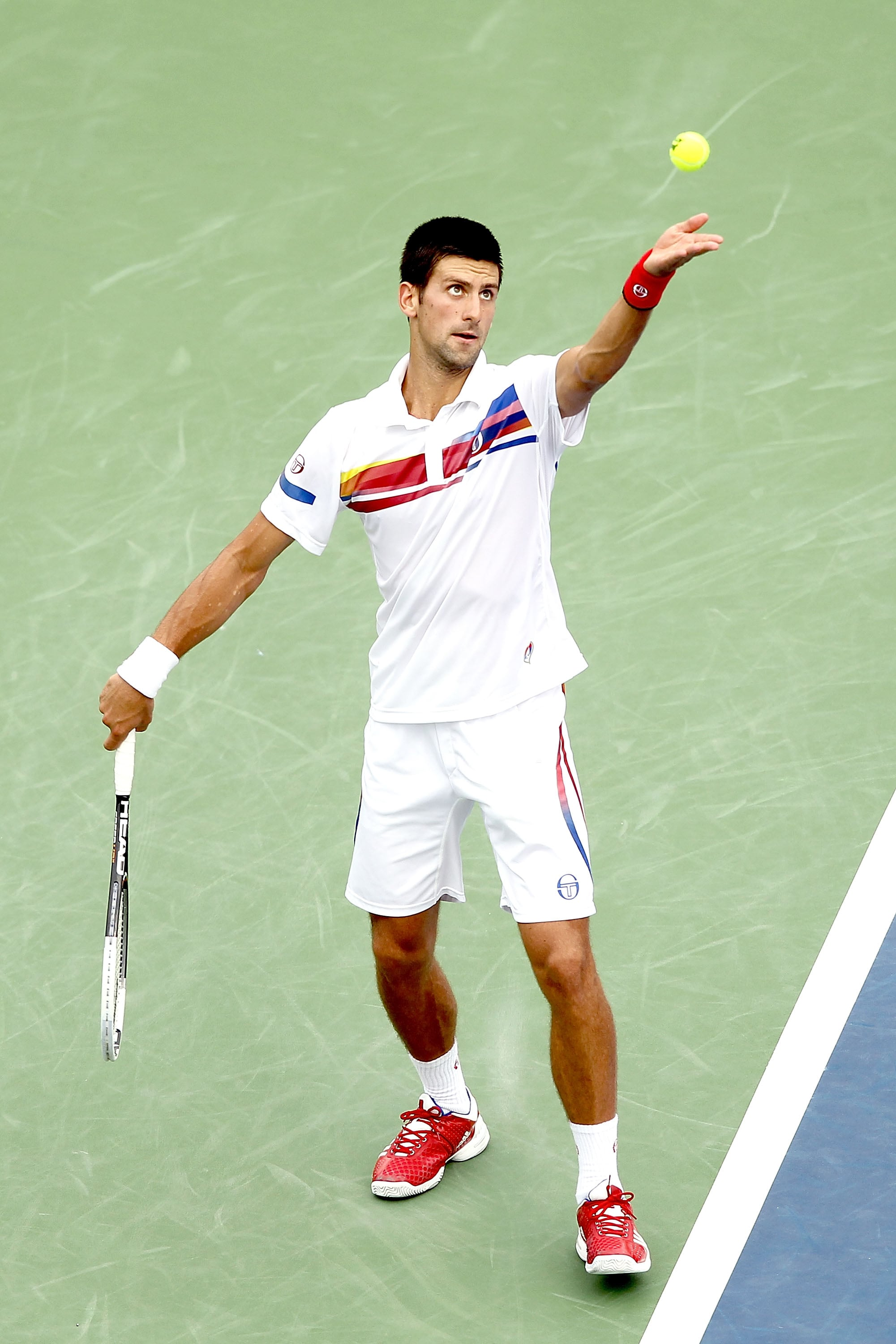 Novak Djokovic paired red tennis shoes with a cool striped shorts and polo shirt combo at the Western & Southern Open in Ohio in August 2011.