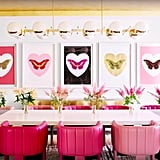 Kylie's dining room features ombre leather chairs, a golden light fixture, and butterfly wall art.
