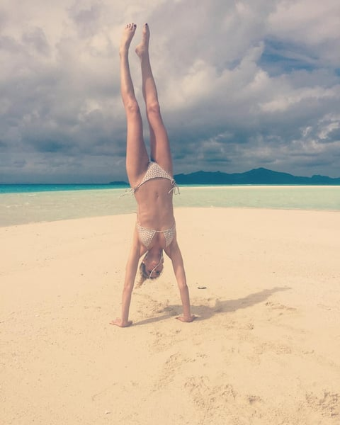 "Whitney performed a handstand in a cream crochet bikini. She captioned her shot, ""What else am I going to do on a deserted island sand quay thingy?!"""