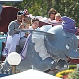 David Beckham held Harper Beckham on his lap with Brooklyn Beckham on a ride at Disneyland.