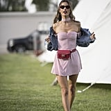 Alessandra Ambrosio wearing a pink minidress by Ale by Alessandra, denim jacket, The Kooples belt bag, and sneakers.
