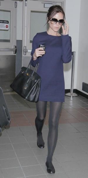 Victoria Beckham Wearing Flats and a Navy Dress at London Heathrow Airport