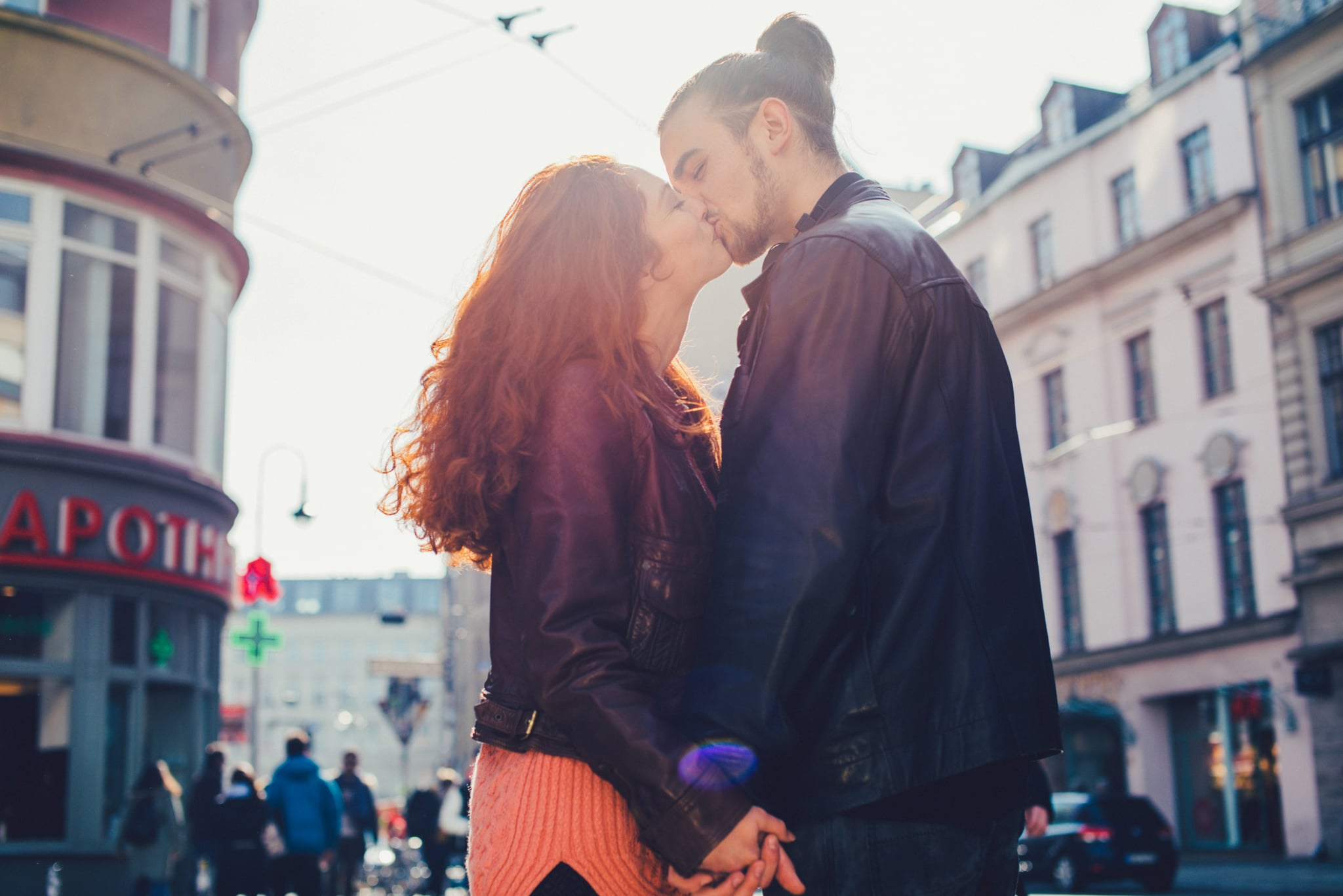 Young couple kissing in the city in backlight.