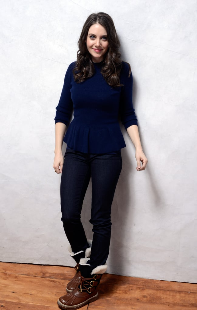 Under her blue belted topper, Alison Brie donned a peplum sweater and trendy duck boots, both by Tory Burch.