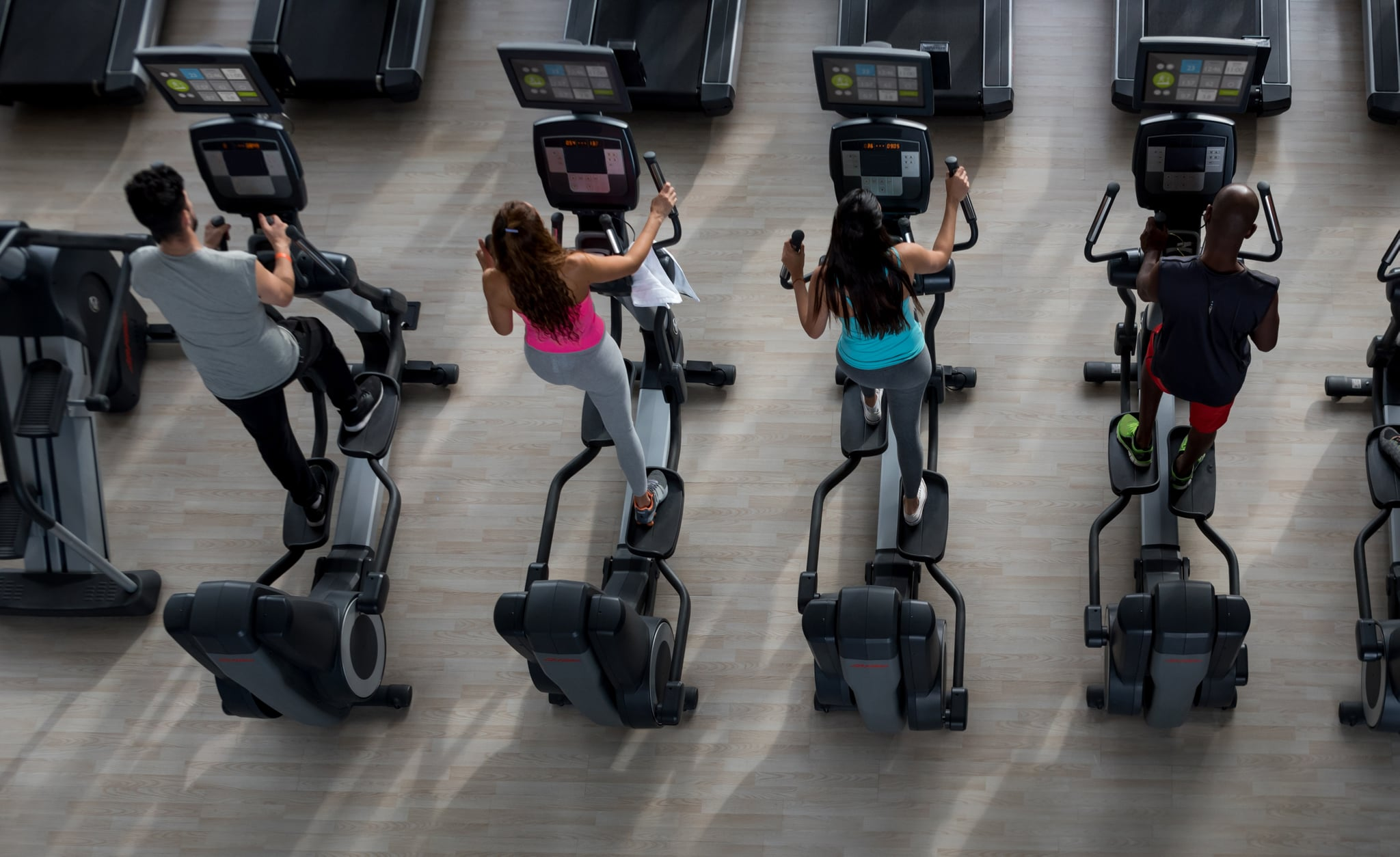 Group of people at the gym on the elliptical machine exercising - High angle view **IMAGES ON SCREEN WERE MADE FORM SCRATCH BY US**