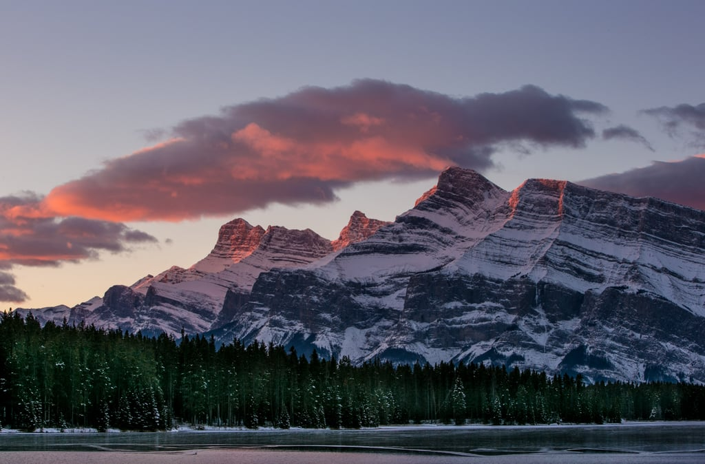 A sunrise in Canada's Alberta province reflected on the snowy mountains.