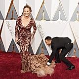 John adorably helped fix Chrissy's dress on the Oscars red carpet in 2016.