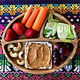 """""""Lunch: iceberg lettuce with Annies Homegrown goddess dressing (our munchkin loves salad because of this dressing), sliced purple grapes, red rice & quinoa cakes with nut butter, raw cashews, strawberries, and carrots."""""""