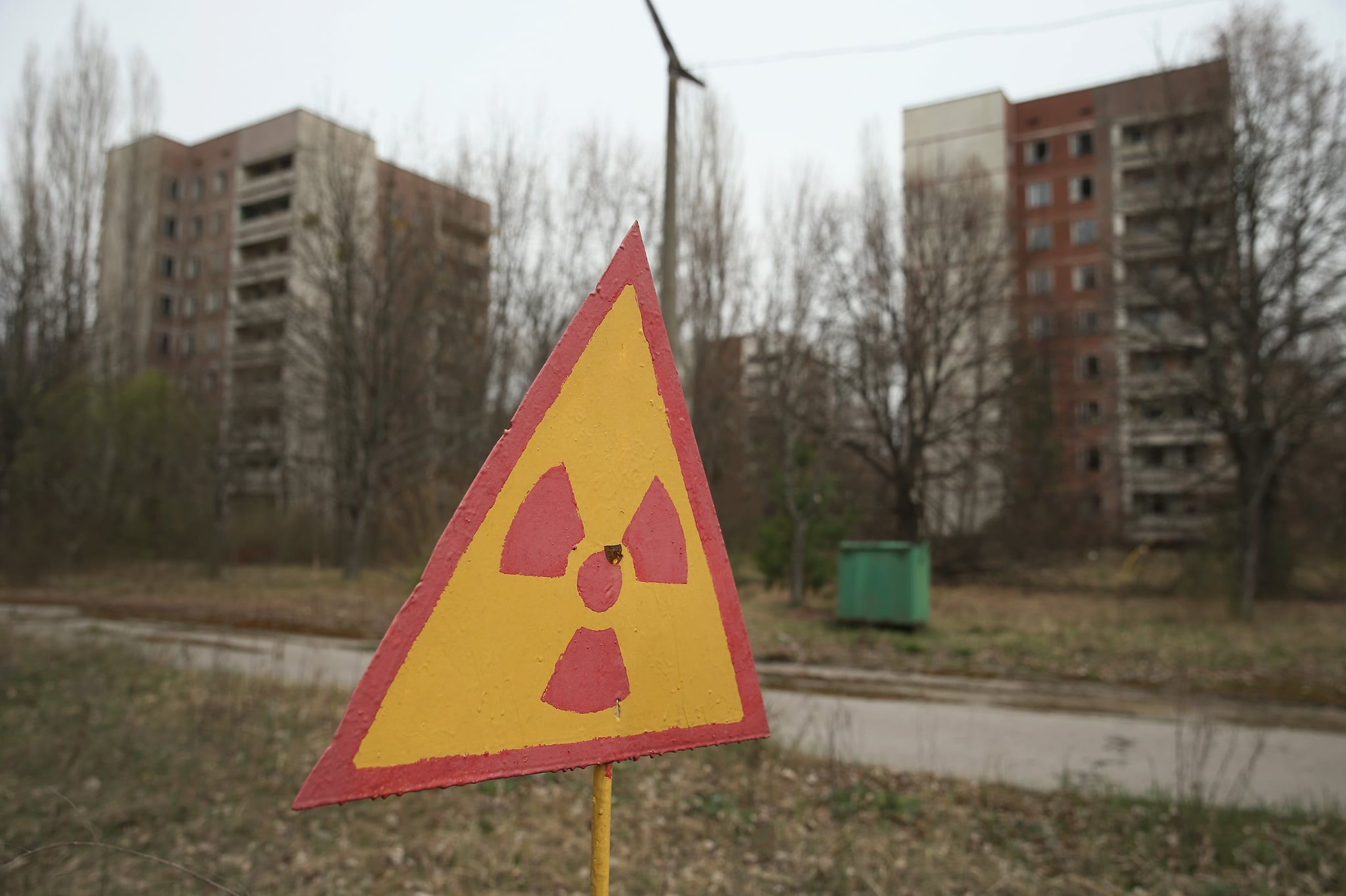 PRIPYAT, UKRAINE - APRIL 09:  A sign warns of radiation contamination near former apartment buildings on April 9, 2016 in Pripyat, Ukraine. Pripyat, built in the 1970s as a model Soviet city to house the workers and families of the Chernobyl nuclear power plant, now stands abandoned inside the Chernobyl Exclusion Zone, a restricted zone contaminated by radiation from the 1986 meltdown of reactor number four at the nearby Chernobyl plant in the world's worst civilian nuclear accident that spewed radiaoactive fallout across the globe. Authorities evacuated approximately 43,000 people from Pripyat in the days following the disaster and the city, with its high-rise apartment buildings, hospital, shops, schools, restaurants, cultural center and sports facilities, has remained a ghost-town ever since. The world will soon commemorate the 30th anniversary of the April 26, 1986 Chernobyl disaster. Today tour operators bring tourists in small groups to explore certain portions of the exclusion zone.  (Photo by Sean Gallup/Getty Images)