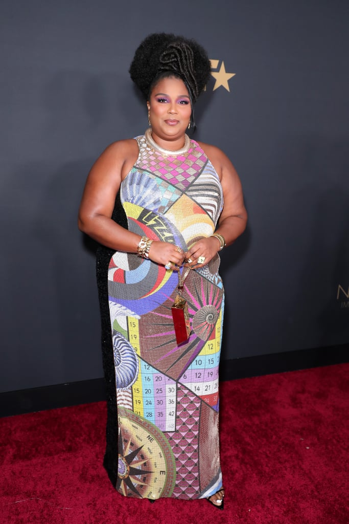 "Lizzo looked ""good as hell"" at the NAACP Image Awards on Saturday night, but what else is new? The ""Truth Hurts"" singer accepted the prize for entertainer of the year during the show, and looked incredible decked out in a custom Mary Katrantzou gown. The dress was designed with geometric shapes covering chainmail and featured Lizzo's name printed across the front — a permanent reminder that this outfit is one of a kind!  Lizzo's stylist, Brett Alan Nelson, tied the look together with pointed sandals from Smash Shoes and a 24K gold bar clutch from Lynn Ban. The bag? Lizzo has it secured. Keep reading for more glimpses of Lizzo's look from all angles."
