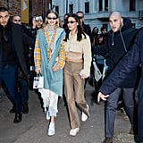 Walking with her sister Gigi wearing a fuzzy cropped jacket and Fendi logo pants from What Goes Around Comes Around.