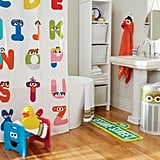 ABC Shower Curtain ($59), Sesame Street Sign Bath Mat ($29), Elmo Hooded Towel ($45), Oscar the Grouch Hamper With Lid ($79), and Cookie Monster and Elmo Step Stool ($76, originally $89)