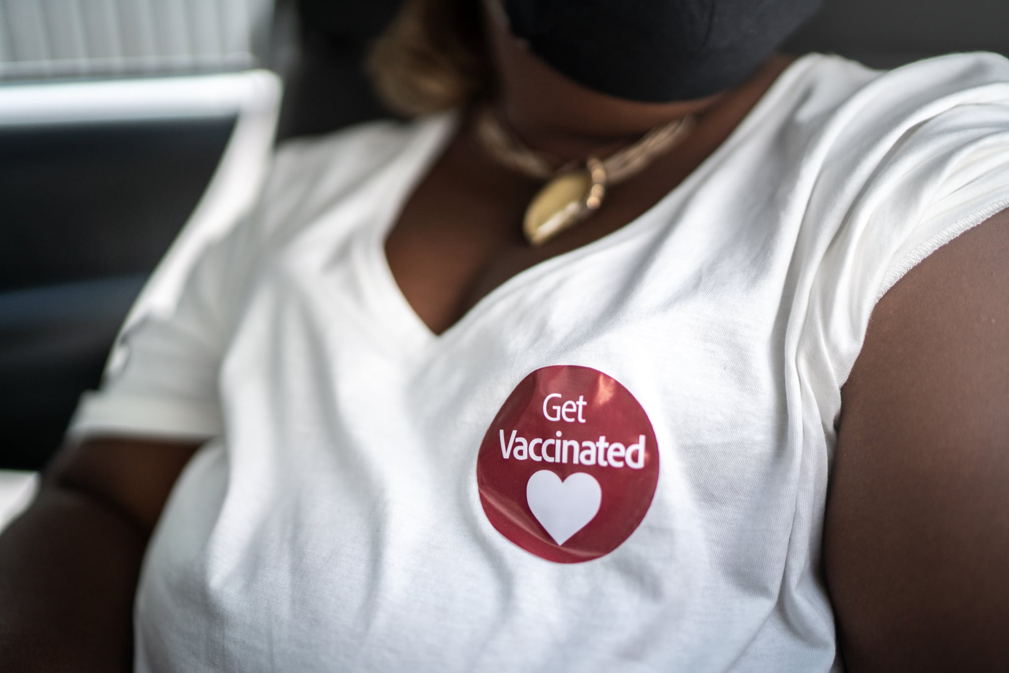 'Get vaccinated' sticker in a woman's shirt in a drive through