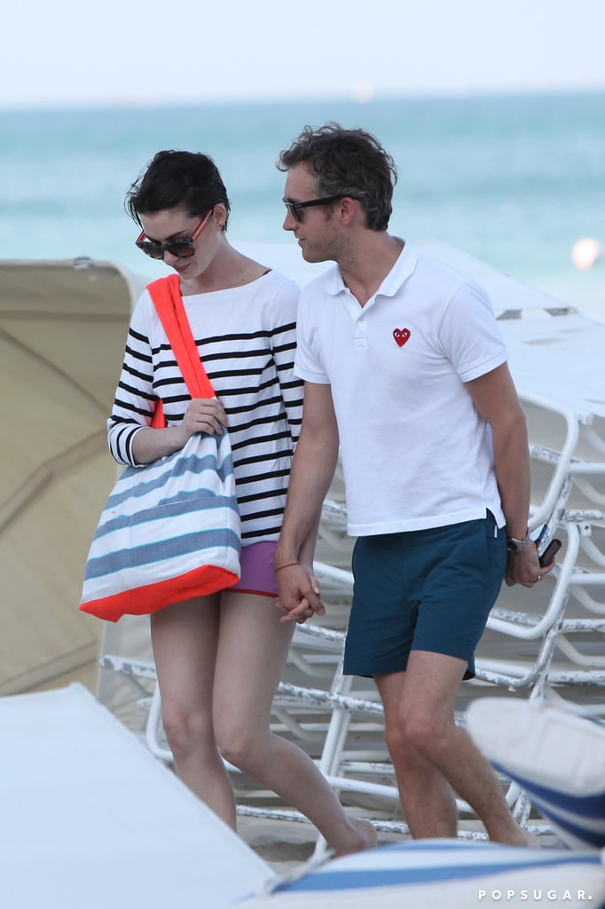 Adam Shulman came to Anne Hathaway's rescue with a warm towel in hand when she finished up her ocean dip in Miami Beach on Sunday. The actress wore a purple one-piece swimsuit and pink shorts for her beach swim with a group of friends. She got playful at one point, tossing a ball to a beachgoer who was on the sand. Adam didn't venture into the ocean, but he did rush up to Anne when she emerged from the water and then held hands with her as they walked back to their hotel. Now that's a considerate husband! Anne spent the weekend in Miami to do press for her new film Rio 2.  She hit the stage to party with her cast at the film's glittering premiere party at the Fontainebleau Hotel and danced adorably while her costar Andy Garcia showed off his impressive conga drum skills. Anne wasn't the only one who got cute at the party, as Jamie Foxx brought a group of children on the stage to teach them how to dance. Anne has been venturing to Miami quite a bit in recent weeks and showed PDA on the beach with Adam during an earlier trip.