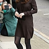 For a visit to The Fostering Network in January 2015, Kate wore a textured chocolate brown Hobbs dress, which she accessorized with black tights, pumps, an elegant clutch, some statement jewels, gold dangling earrings, and her gorgeous sapphire ring.
