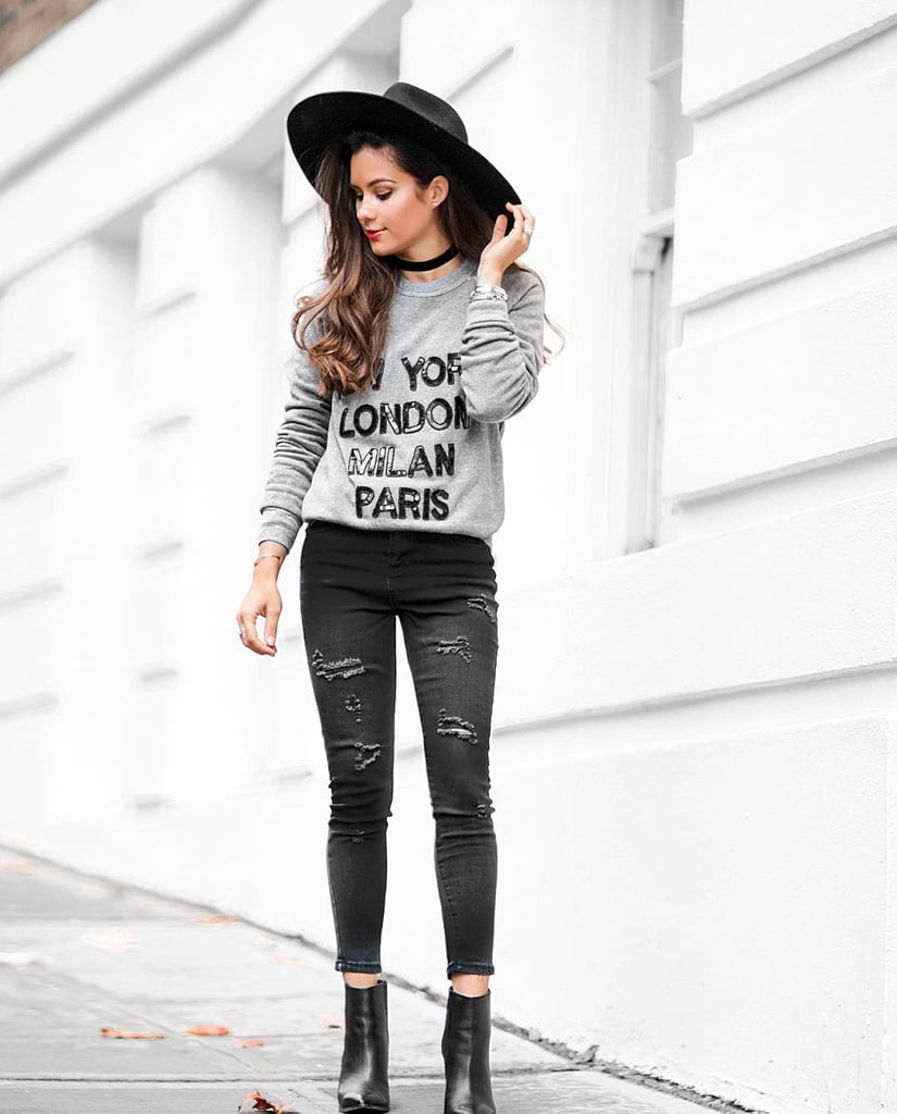 A Graphic Sweatshirt, Black Jeans, Black Boots, and a Wide-Brim Hat