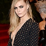Cara Delevingne stayed on point with spiked earrings and layered necklaces to accompany her studded Burberry gown.