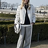 This showgoer kept her sleek black and white palette consistent, from her striped wide-leg trousers to her top, jacket, and clutch.
