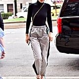 Gigi Hadid Wearing Silver Prada Trousers and a Black Wolford Bodysuit