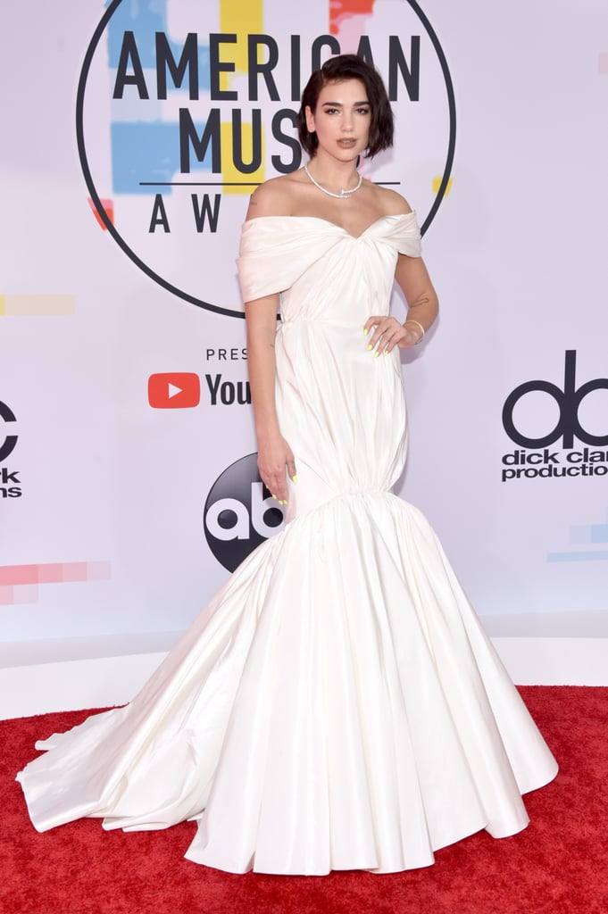 "It's hard to resist falling in love with Dua Lipa's American Music Awards gown. The 23-year-old British singer left her rebellious alter-ego ""Electra"" at home while she walked the red carpet in a delicate outfit on Oct. 9. She opted for an off-the-shoulder gown, that cinches at her knees in a mermaid-style silhouette.  Could this all-white outfit be a nod to her sweet ""angel"" shoulder tattoo? She certainly looks heavenly. To give the stunning ensemble an edgy twist, Dua paired the dress with a necklace resembling a metal nail. Keep reading to see her AMAs gown from all angles, and make sure you check out more of the sexiest red carpet looks."