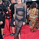 Erin Wasson was not shy to put her figure — and daring style — on display in a sheer black dress as she stepped onto the VMAs red carpet. She completed her look with a turban-inspired headband and black strappy sandals.