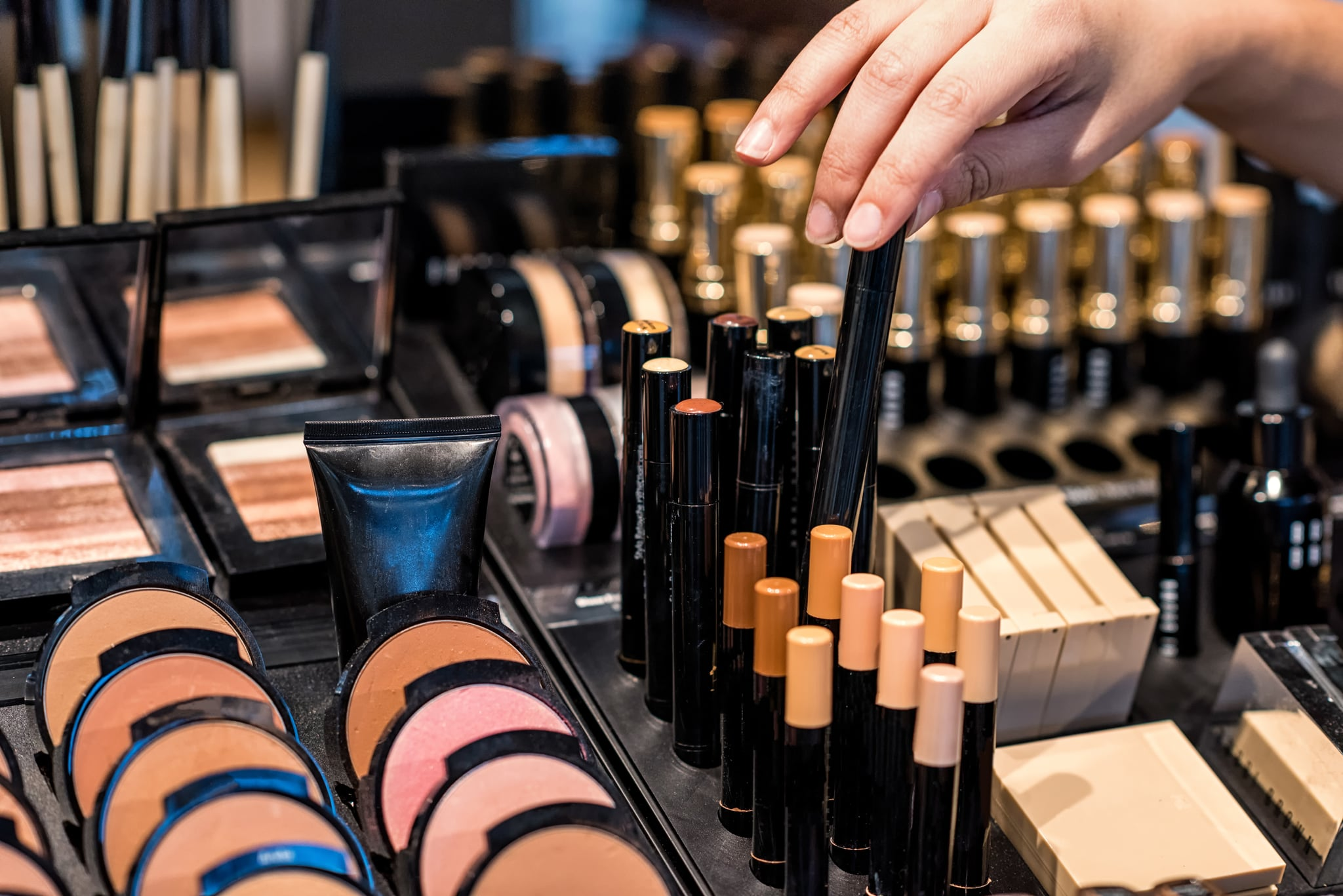 A woman's hand with bracelets chooses from various shades of make-up at a high-end makeup counter.