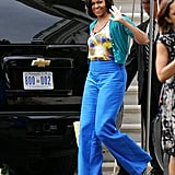 The first lady attended an event at the Sidwell Friends School in a cute, colorful look. She paired cobalt trousers with a printed tank and topped it with a turquoise sweater.