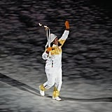 A torchbearer enters the stadium.
