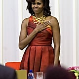 Michelle Obama was fabulous as ever in a sunset-print, one-shoulder Naeem Khan dress and Robert Lee Morris gold necklace during a dinner in South Africa.
