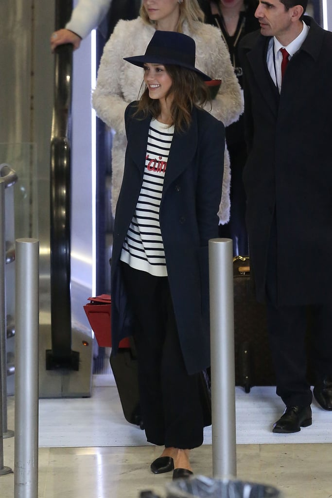 "The centerpiece of Jessica Alba's très chic travel style was her striped and sequined ""Je T'aime"" sweater, which she finished with D'Orsay flats and a classic coat."